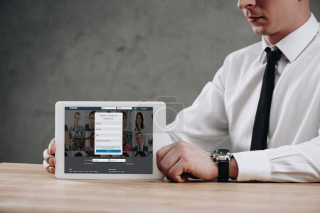 cropped shot of businessman holding digital tablet with linkedin website on screen