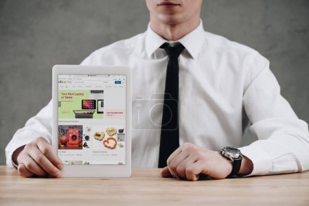 Photo for Cropped shot of businessman holding digital tablet with ebay website on screen - Royalty Free Image