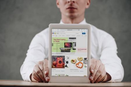 cropped shot of man holding digital tablet with ebay website on screen