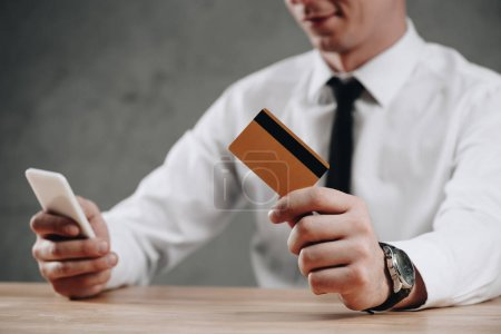 cropped shot of businessman holding credit card and using smartphone