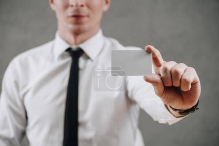 cropped shot of businessman holding blank card on grey