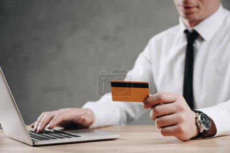 cropped shot of businessman holding credit card and using laptop
