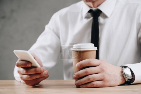 cropped shot of businessman holding paper cup and using smartphone