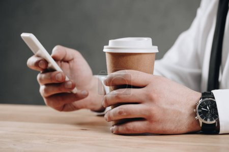 close-up partial view of businessman holding paper cup and using smartphone