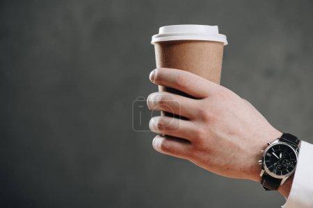 Photo pour Recadrée tir d'homme d'affaires détenant la tasse de papier avec le café pour aller sur fond gris - image libre de droit