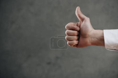 Photo for Cropped shot of man showing thumb up on grey - Royalty Free Image