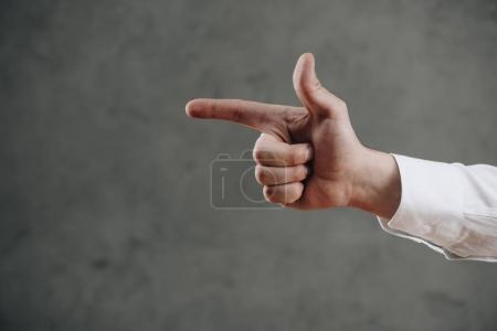 Photo for Close-up partial view of man pointing away with finger on grey - Royalty Free Image