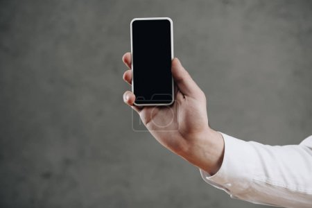 cropped shot of man holding smartphone with blank screen on grey