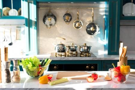 fresh vegetables and spices on table in empty kitchen