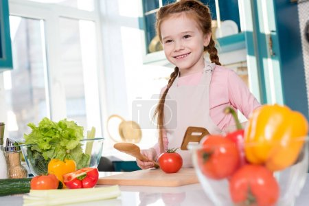 cute happy kid in apron cooking in kitchen