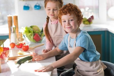 beautiful happy children in aprons cooking together in kitchen