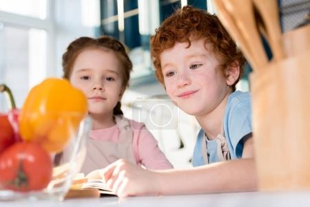 selective focus of cute little kids cooking together in kitchen