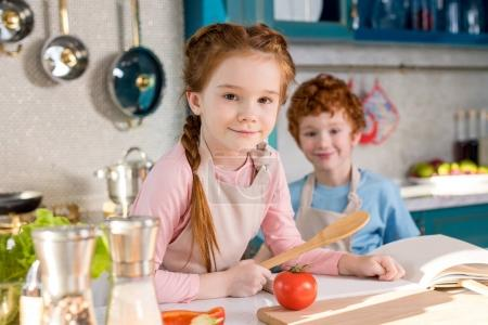 adorable children smiling at camera while cookign together in kitchen
