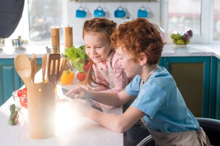 happy children using digital tablet while cooking together in kitchen