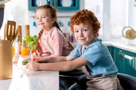 adorable happy children smiling at camera while cooking together in kitchen