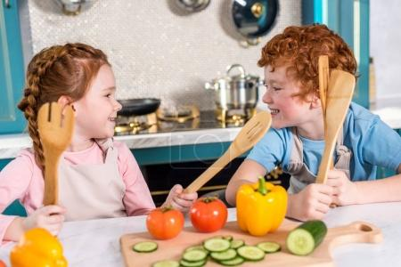 happy kids with wooden utensils smiling each other while cooking together in kitchen