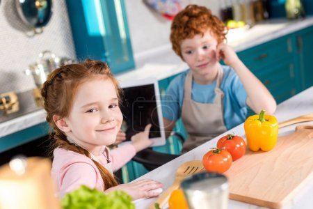 children using digital tablet while cooking together in kitchen
