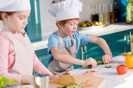 children in chef hats and aprons preparing vegetable salad together in kitchen