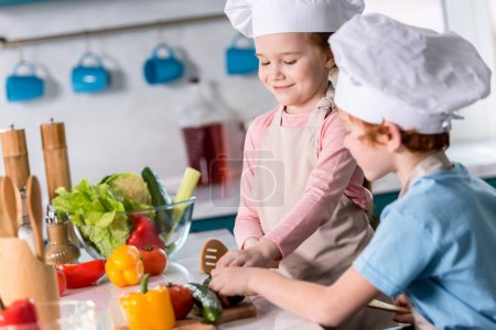 cute little kids in chef hats preparing vegetable salad together in kitchen