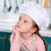 pensive little child in chef hat holding hand on chin and looking away in kitchen