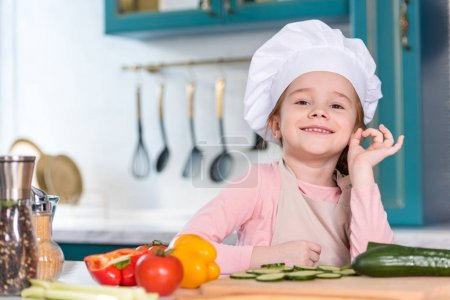adorable child in chef hat showing ok sign and smiling at camera in kitchen