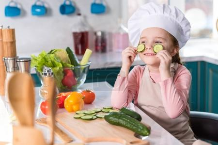 kid in chef hat and apron holding slices of cucumber while cooking in kitchen