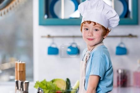 cute little boy in chef hat and apron smiling at camera in kitchen