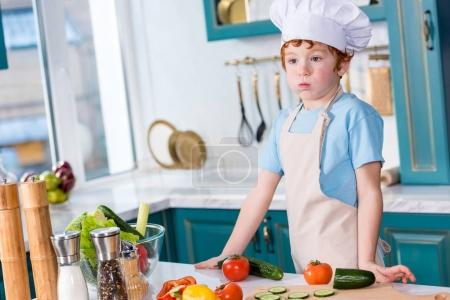 cute little boy in chef hat and apron looking away while cooking in kitchen