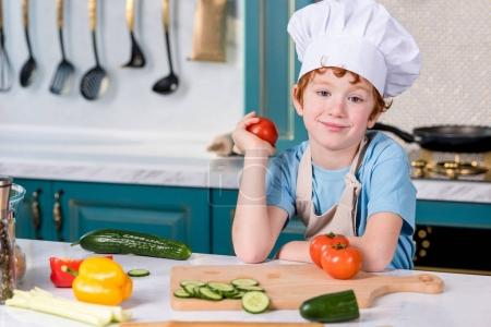 cute little boy in chef hat and apron smiling at camera while cooking in kitchen