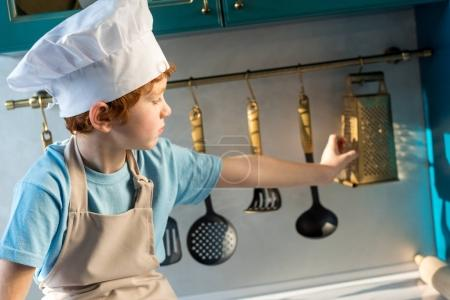 Photo for Adorable little boy in chef hat and apron looking at utensils while sitting in kitchen - Royalty Free Image