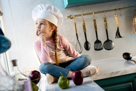 Photo for Pensive kid in chef hat looking away while sitting in kitchen - Royalty Free Image