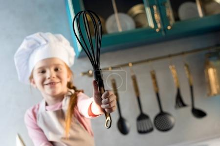 close-up view of smiling child in chef hat holding whisk in kitchen