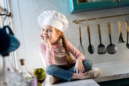 adorable child in chef hat sitting in kitchen and smiling at camera