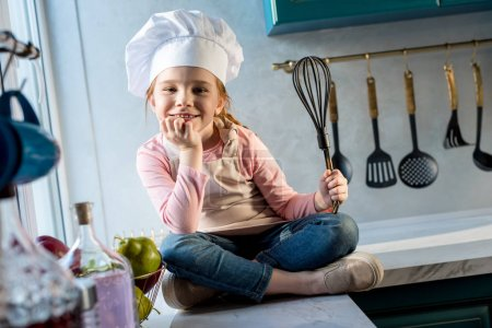 cute child in chef hat holding whisk and smiling at camera in kitchen