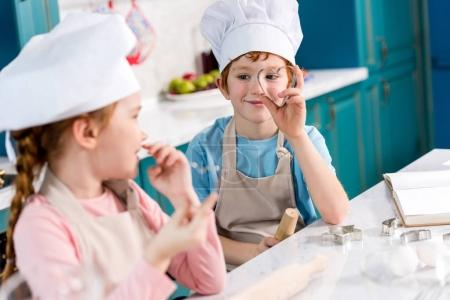 adorable children in chef hats and aprons smiling each other while cooking together in kitchen