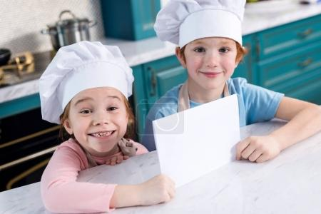 cute little children in chef hats holding blank card and smiling at camera