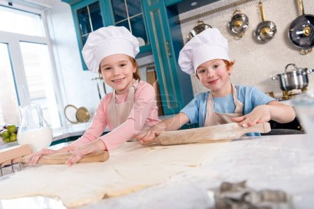 Photo for Children preparing dough and smiling at camera in kitchen - Royalty Free Image