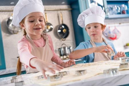 Photo for Adorable little kids in chef hats and aprons preparing cookies together - Royalty Free Image