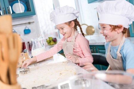 happy little children in chef hats preparing cookies together in kitchen