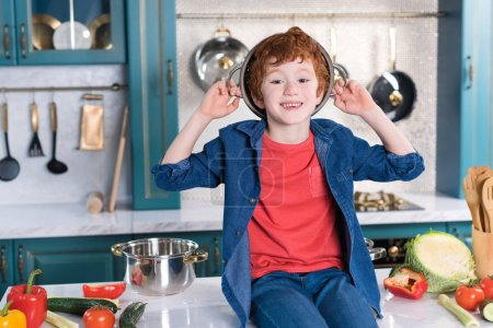 adorable little boy with pan on head smiling at camera while sitting on kitchen table