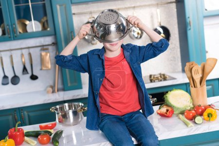 Photo for Cute little boy with pan on head sitting on kitchen table - Royalty Free Image