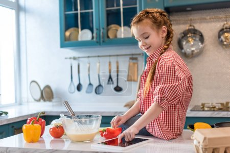 Photo for Cute smiling child using digital tablet while cooking in kitchen - Royalty Free Image