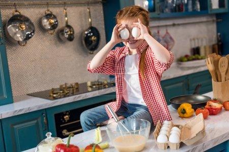 Foto de Lindo niño sujetando huevos y sonriendo en la cocina - Imagen libre de derechos