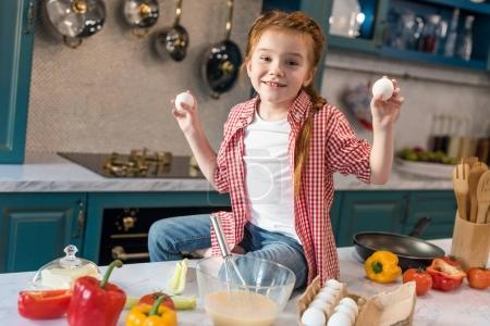 cute little child holding eggs and smiling at camera in kitchen