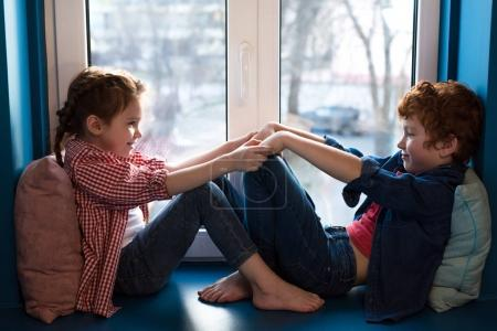 adorable little kids holding hands and smiling each other while sitting on windowsill