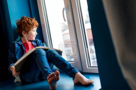 cute barefoot boy with book sitting on windowsill