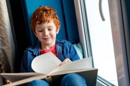 Photo pour Mignon sourire petit garçon lecture livre tout en étant assis sur le rebord de la fenêtre - image libre de droit
