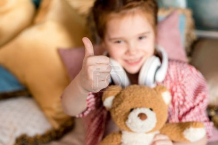 cute little child in headphones holding teddy bear and showing thumb up