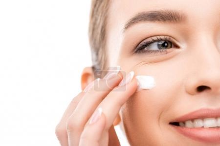 Photo pour Vue recadrée de la jeune femme appliquant la crème cosmétique, isolé sur blanc - image libre de droit