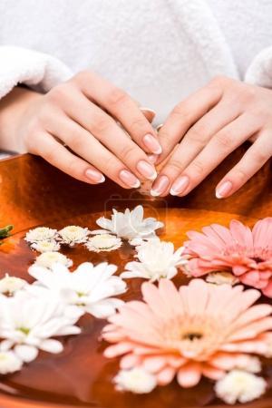 Photo pour Recadrée vue de femme faisant des procédure de spa avec fleurs, concept de soins des ongles - image libre de droit